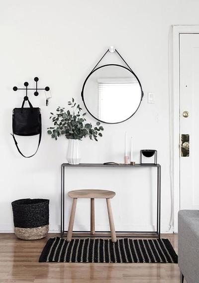 Hall de entrada minimalista com aparador preto e espelho redondo