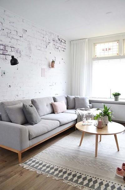 sala com decoração minimalista com sofá cinza e tapete