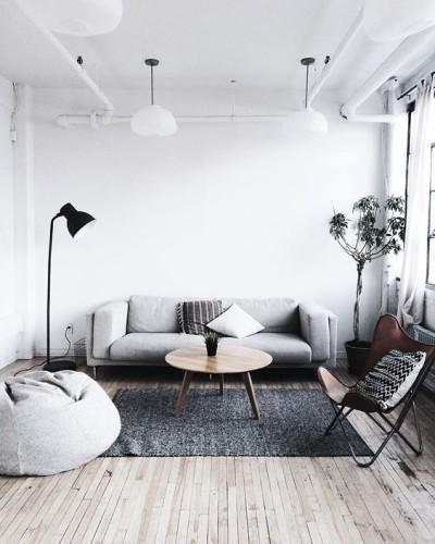 sala grande com sofá cinza, pufe, cadeira e planta