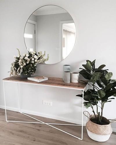 Aparador de ferro e madeira com espelho redondo e plantas