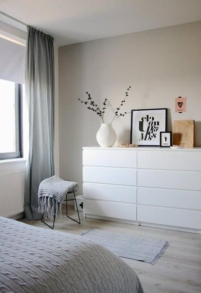 Cômoda branca com quadros e vaso