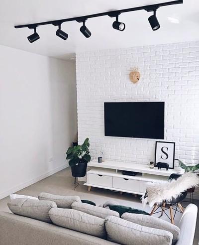 Sala com decoração minimalista com rack e sofá cinza
