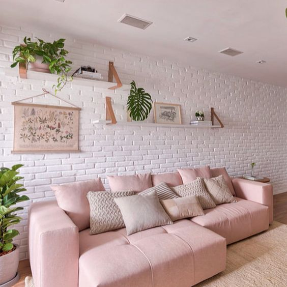 sofá rosa em sala com parede de tijolinhos branco