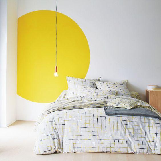 Pinturas de paredes diferentes - Quarto com pintura criativa na parede em formato circular amarelo.