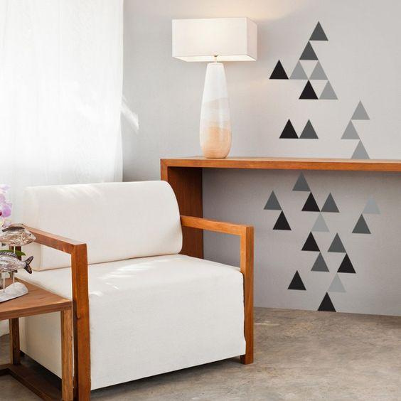 Canto da sala com pintura geométrica na parede em formato triangular.