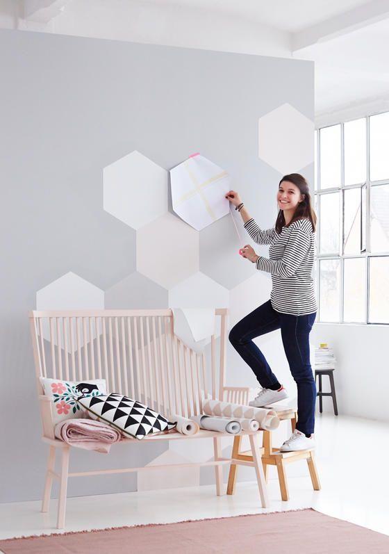 Pinturas de paredes diferentes - Mulher mostrando como fazer uma pintura de parede geométrica hexagonal.