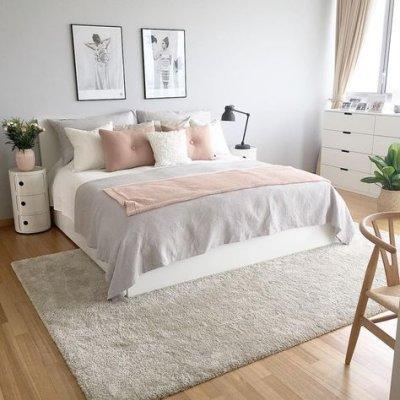 Tom pastel no quarto com cama e almofadas, tapete grande e quadros na parede.