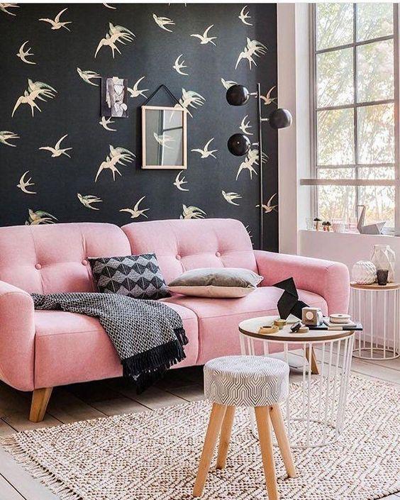 Sofá rosa em parede preta
