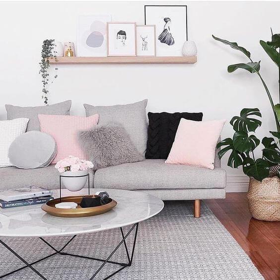 Sofá com almofadas, tapete e prateleira com quadros na parede.