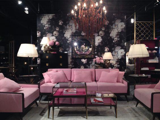 Ambiente com sofá rosa e lustre grande e abajures laterais.