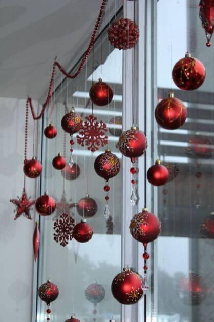 Bolas de Natal penduradas na janela.