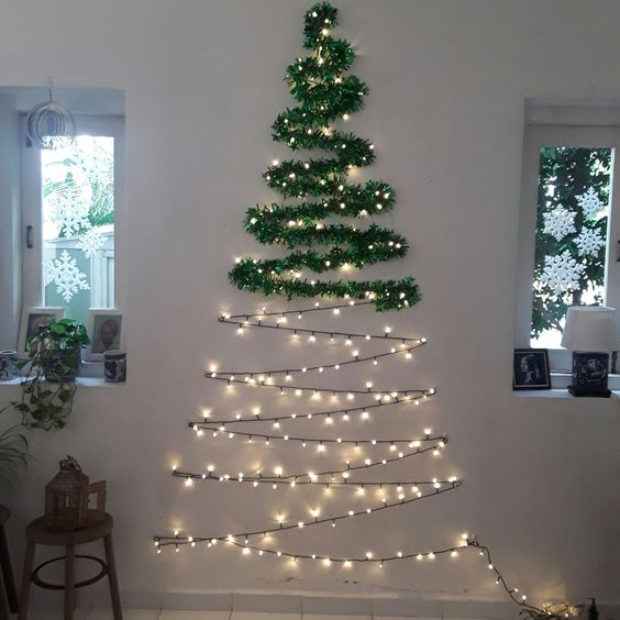 Decoração de Natal com árvore criativa na parede e pisca pisca