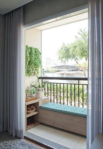 Varanda de apartamento com jardim vertical, banco com futon.