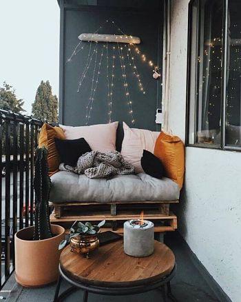 Decoração de varanda pequena com pallets, manta, luzes, futons e almofadas.
