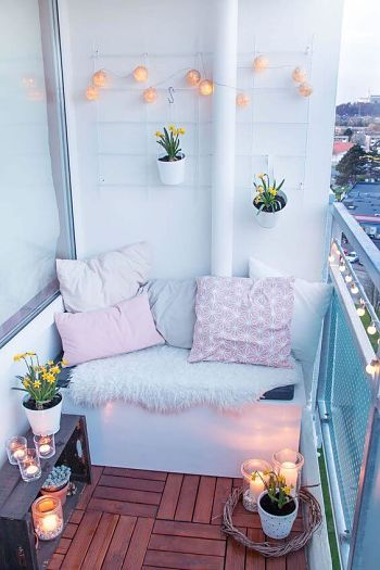 Decoração de varanda pequena com luzes pendentes, manta e almofadas.