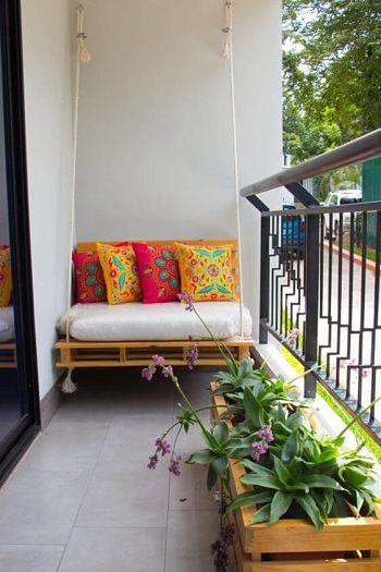 Decoração de varanda pequena com pallet suspenso e almofadas.