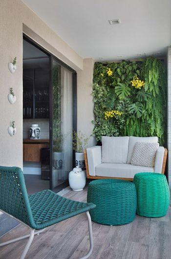 Decoração de varanda pequena com jardim vertical e bancos.