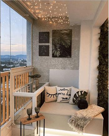 Decoração de varanda de apartamento com almofadas e manta.
