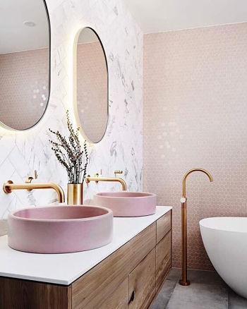 Banheiro com duas cubas, dois espelhos redondos e pastilhas pequenas na parede.