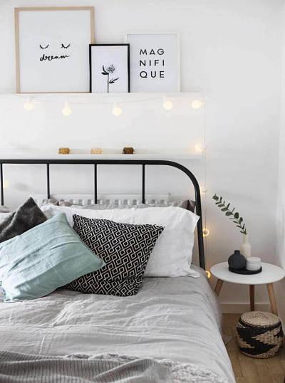 Decoração de quarto de casal simples com quadros e luminária de bolas
