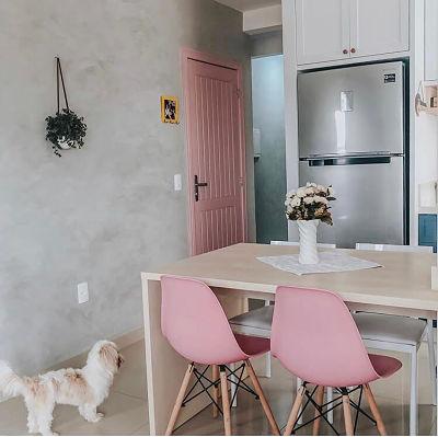 Cimento queimado na parede de sala com cadeira eames e porta rosa