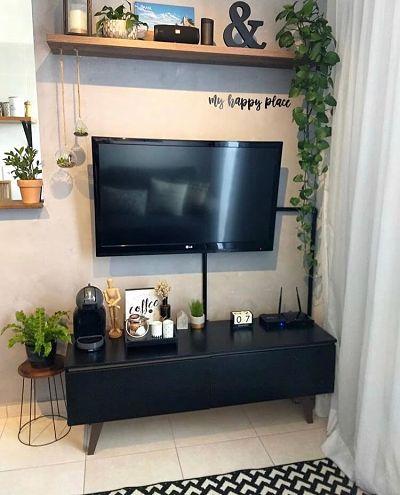 Parede cimento queimado na sala com rack, tv e plantas