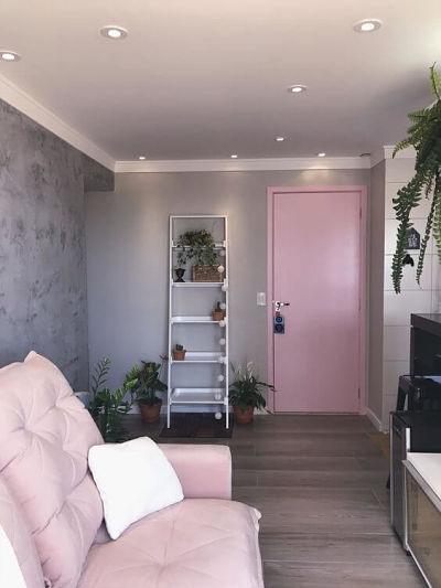 Sala com sofá rosa, porta rosa e parede de cimento queimado