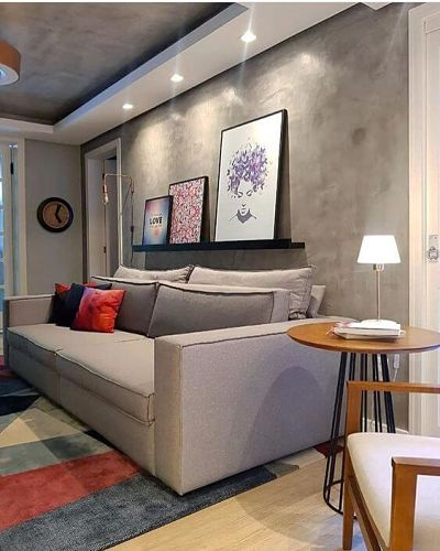 Sala com quadros e sofá cinza e parede de cimento queimado
