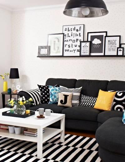 Sala com sofa preto em L e almofadas e quadros na parede