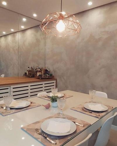 Sala de jantar com textura de cimento queimado e luminária rose gold
