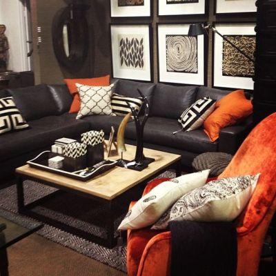 Sala com sofá preto e amofadas coloridas