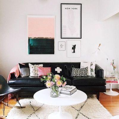 Sofá preto de couro na sala com almofadas e quadros