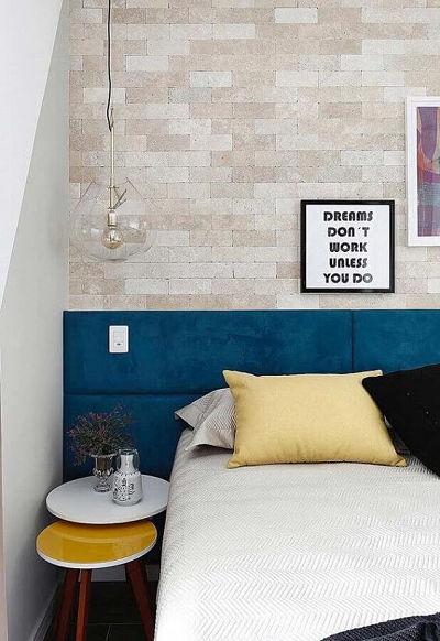 Cabeceira estofada azul e parede de tijolinho