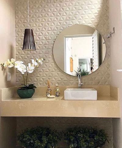 Banheiro com cuba de apoio, espelho redondo e revestimento 3d na parede