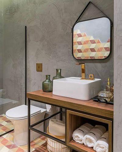 Banheiro pequeno com bancada de madeira com cuba de apoio e parece de cimento queimado