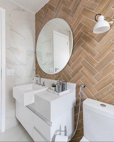 Banheiro com espelho redondo e pia de semi encaixe branca