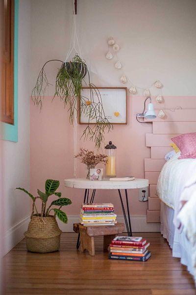 Quarto com pintura de meia parede rosa e plantas.