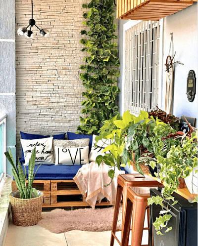 Varanda pequena com plantas, paletes e futton.