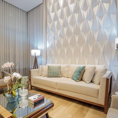 Sala com sofá branco e almofadas e gesso 3d na parede.