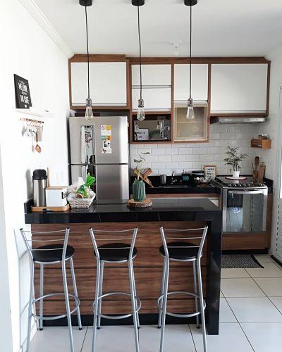 Cozinha americana pequena com banquetas e luminária pendente