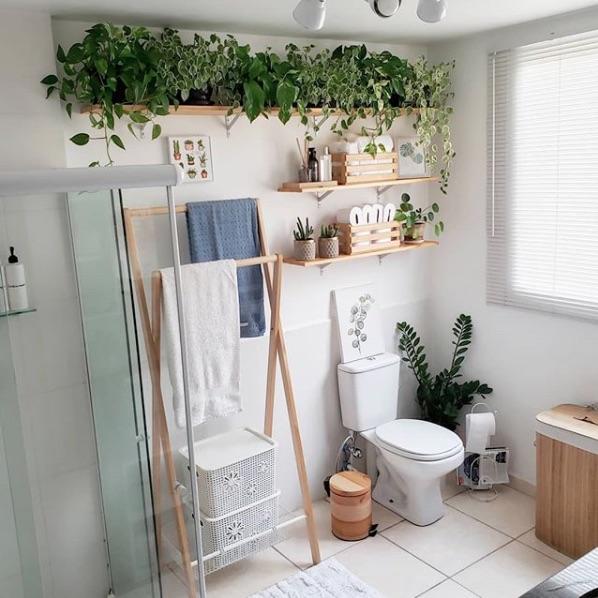 Decoração de banheiro alugado com plantas e prateleiras de madeira.