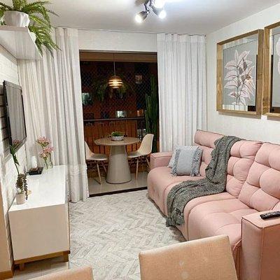 Sofá retrátil rosa em sala pequena e varanda no fundo
