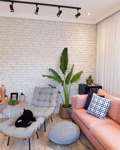 Sala com sofá rosa, parede de tijolinho, poltrona cinza e planta