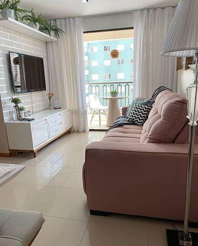 Sala pequena de apartamento com sofá rosa claro