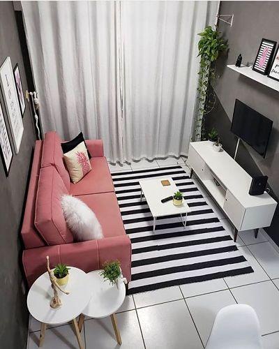 Sala com sofá rosa e paredes escuras