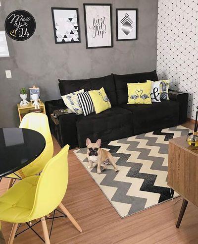 Sala com sofá preto e almofadas amarelas
