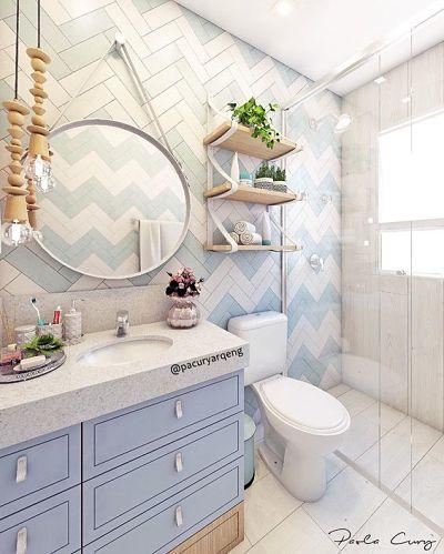 Banheiro pequeno tons claros, prateleiras e espelho redondo.