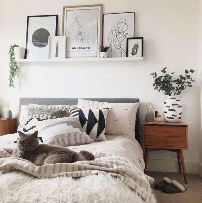 Decoração de quarto com prateleira e quadros na parede.