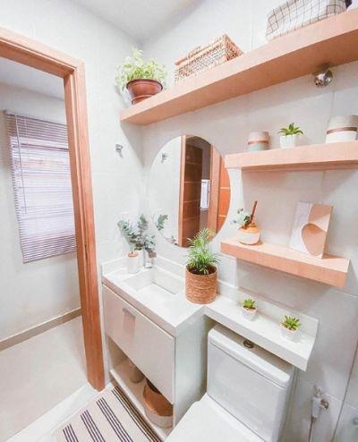Banheiro pequeno com prateleiras de madeira
