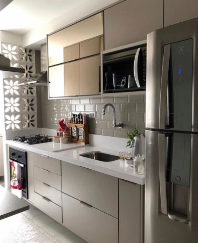 cozinha planejada marrom com bancada branca, cooktop e forno embutido